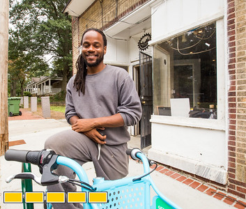 Shawn Walton, the founder of WeCycle, is riding a Relay Bike Share bike, available for rent in front of his shop, in Gordon White Park.  WeCycle is a bike shop and community center were footballs, yoga mats, toddler toys and bikes can be checked out.  The center is working with students from Morehouse college of Medicine to continue it's community efforts.  (Jenni Girtman / Atlanta Event Photography)