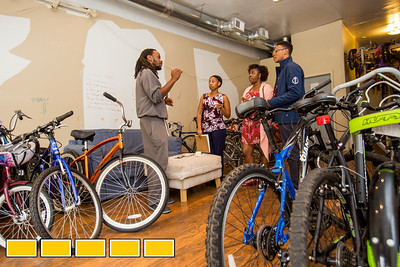 Shawn Walton, left, is the founder of WeCycle, a bike shop and community center were footballs, yoga mats, toddler toys and bikes can be checked out.  The center is working with students from Morehouse college of Medicine, including public health master degree students Demetrius Geiger, second from left, Kiara Sims-Thrasher, pink dress, and Darryl Howard, far right, to continue community efforts.  (Jenni Girtman / Atlanta Event Photography)