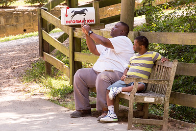 Camp Best Friends counselor Michael Jennings, left, takes a photo of a camper on horseback with his student Nathan Benefield, 22, right, at Chastain Horse Park.  The center provides therapeutic programs for special needs campers and for those in need of physical and occupational therapies.  The program is comprised of professional therapist, equestrians and volunteers.    (Jenni Girtman / Atlanta Event Photography)