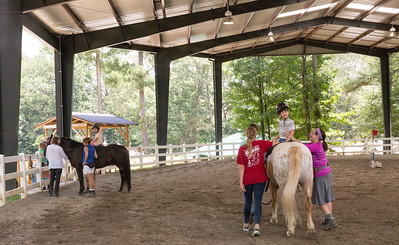 Trett Johnson, 8, rides during a physical therapy session at Chastain Horse Park.  The therapy is guided by professional physical and occupational therapist and is not intended to teach horseback riding.  The hippotherapy part of the center it is about using the horse as a tool for physical therapies.  The center provides therapeutic programs for special needs campers and for those in need of physical and occupational therapies.  The program is comprised of professional therapist, equestrians and volunteers.    (Jenni Girtman / Atlanta Event Photography)