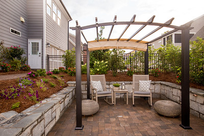 Making great use of a small outdoor space, Diane and Dave Miller have transformed what was once a drainage issue into space for outside dining well into the Fall with a large fireplace and adapatable shading.  Clever design incorporates a bench built into the landscaping for entertaining and green space for the couple's two dogs Emily and Lexie.  (Jenni Girtman / At;anta Event Photography)