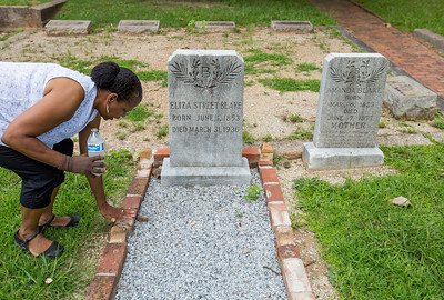 DL Henderson, a writer and Oakland Cemetery board member, is in the African American burial grounds at the grave site of Eliza Blake, a domestic worker who died at 83 years old and left a sizable sum to her church when she passed away.  Her site is unique in that a brick boarder, or cradle exists at all (not common for the time and tradition) but also that it is 3 and sometimes 4 bricks deep.  Recent rennovations have brought back up the sinking cradle where Blake is buried with her family in Oakland block 68.  (Jenni Girtman / Atlanta Event Photography)