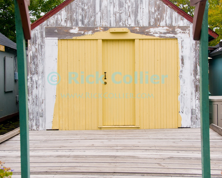 """""""Beach Shack (Yellow)"""" - Where once there were seasonal tents, some have now built wooden """"shacks"""" where they can stay when visiting the beach in summer.<br /> <br /> <br /> USA """"New Jersey"""" NJ """"Ocean Grove"""" Ocean Grove sidewalk shack tent camping seasonal summer stay lodging property poles posts doors color colorful colors yellow deck decks wood frame framework"""