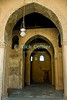 "Cairo, Egypt -- A wooden door stands at the back of a series of arched arcades, on the Qibla side of the historic ibn Tulun mosque. © Rick Collier / RickCollier.com.<br /> <br /> <br /> <br /> <br /> <br /> travel; vacation; tour; tourism; tourist; destination; Egypt; Cairo; mosque; madrassa; Tulun; ""ibn Tulun""; door; wood; lamp; light; arch; arches; arcade; arcades"