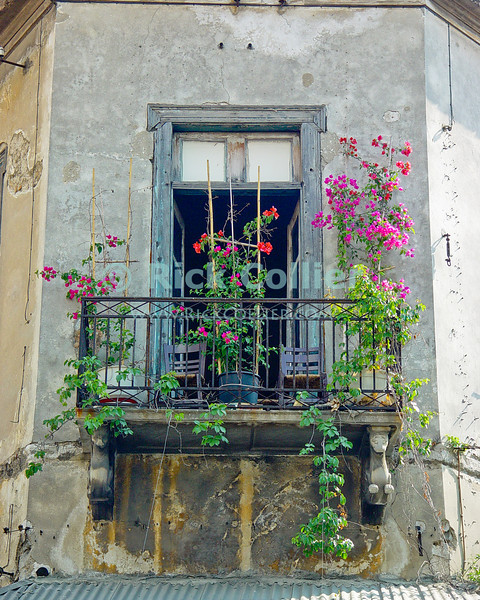 Athens, Greece.  Flowers decorate a second storey iron-railed balcony, where two chairs await their evening occupants.   © Rick Collier<br /> <br /> <br /> <br /> <br /> <br /> Greece Athens window windows shutter shutters flower flowers door doors