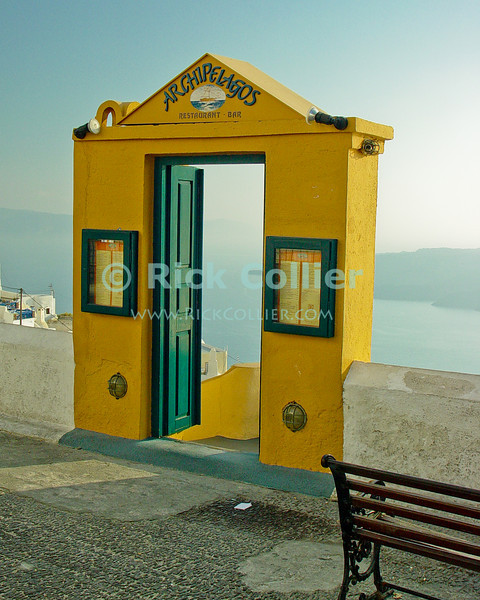 Fira Town, Santorini, Greece.  The entrance to a restaurant below, this door appears to lead nowhere but offers spectacular views of the ocean and caldera far below.  Santorini is one of several islands that ring the blown-out remains of an ancient volcano, rising from the deep ocean in the Aegean Sea.  The volcano exploded, leaving several islands surrounding a very deep patch of sea -- actually once the caldera of the volcano.  The two large towns on Santorini, Oia and Fira towns, overlook the caldera.  © Rick Collier<br /> <br /> <br /> <br /> <br /> <br /> Greece Santorini Fira cliff cave home caldera Aegean Sea ocean sun stairs steps bright colors door doors window windows wall window windows door doors shutter shutters view cafe taverna restaurant shop store