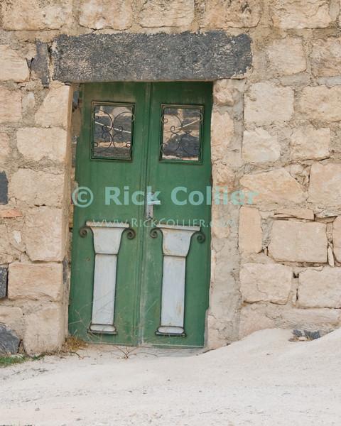 Umm Qais, northwestern Jordan:  A crooked door blocks off one of the buildings that is being reconstructed at the biblical town of Gadara.  © Rick Collier<br /> <br /> <br /> <br /> Jordan 'Umm Qais' Ottoman Roman Gadara Gadarenes Bible Biblical ruin ruins 'ancient world' archeology 'archeological site' window antique shutter door