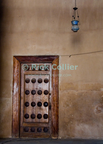 """Cairo, Egypt -- A door and lamp in the wall of the Qibla side of the historic ibn Tulun mosque. © Rick Collier / RickCollier.com.<br /> <br /> <br /> <br /> <br /> travel; vacation; tour; tourism; tourist; destination; Egypt; Cairo; mosque; madrassa; Tulun; """"ibn Tulun""""; door; wood; lamp; light;"""