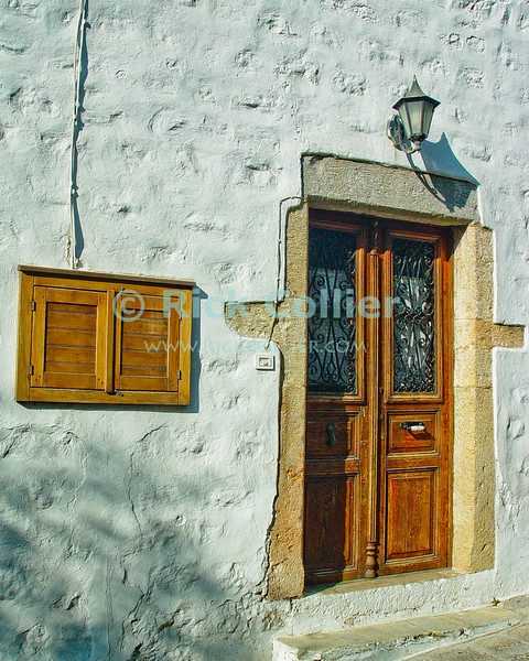 Patmos, Greece.  Near the monestary on Patmos, it is easy to wander into a warren of small alleys, lined with neatly maintained windows and doors.  © Rick Collier<br /> <br /> <br /> <br /> <br /> <br /> Greece Patmos cross religion Christian John Saint John the Theologian 'St John' revelation Bible Biblical Book of Revelations cave holy site shrine olive tree window windows monestary courtyard window windows door doors narrow alley alleyway