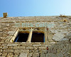 Lyndos, on the island of Rhodes, Greece.  Empty windows look out of the partially reconstructed chapel, on the acropolis at Lyndos.  © Rick Collier<br /> <br /> <br /> <br /> <br /> <br /> Greece Lyndos harbor inlet ocean Aegean Sea boat boats view tour tourist tourism tourists acropolis Roman Empire Hellenistic Crusader fort fortification ruin ruins archeology archeological acropolis window wall