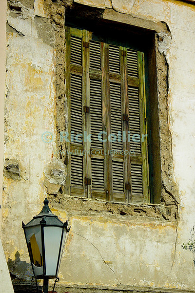Athens, Greece.  Damaged louvered shutters protect the interior of a home from heat of the harsh afternoon sun.   © Rick Collier<br /> <br /> <br /> <br /> <br /> <br /> Greece Athens window windows shutter shutters light lamp post lamppost