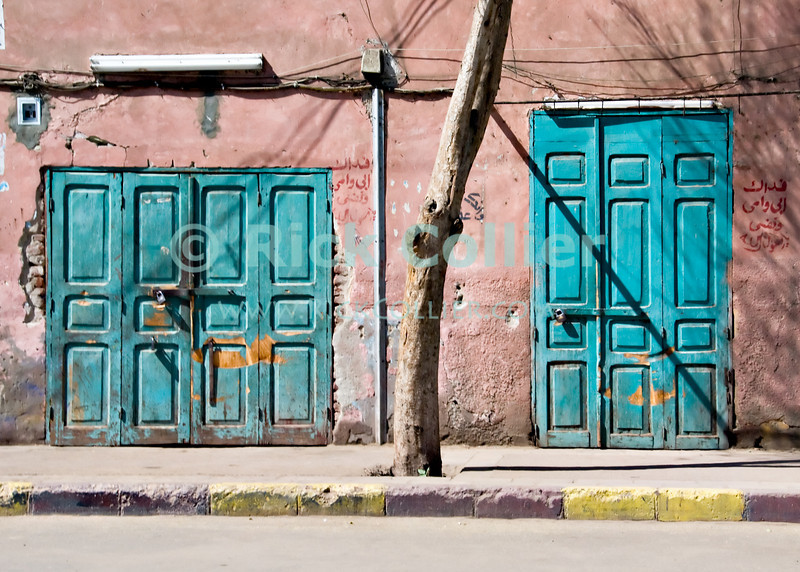 Edfu, Egypt -- Closed. © Rick Collier / RickCollier.com.<br /> <br /> <br /> <br /> travel; vacation; tour; tourism; tourist; destination; Egypt; Edfu; door; doors; lock; curb; sidewalk