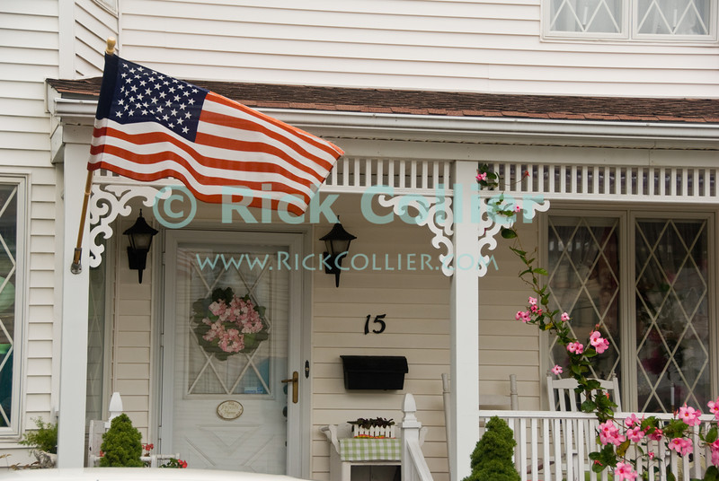"""Home Flag"" - A flag and flowering climatis vines adorn the railing and deck of a home at Ocean Grove, New Jersey, USA.<br /> <br /> <br /> USA ""New Jersey"" NJ ""Ocean Grove"" Ocean Grove sidewalk house home deck porch railing post flower flowers Climatis vine flag ""stars and stripes"""