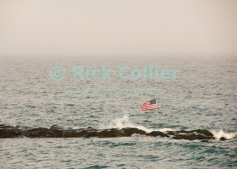 """Flag"" - An American flag flies from the end of the breakwater at Allenhurst, New Jersey, USA.<br /> <br /> <br /> USA ""New Jersey"" NJ Allenhurst beach Atlantic ocean wave fog mist jetty breakwater stones rocks American flag waving"