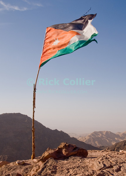At the overlooks atop Petra, a Jordanian flag flies above views of the Jordan river valley and Galilee.  © Rick Collier<br /> <br /> <br /> <br /> Jordan Petra Nabatea Nabatean Rome Roman ruin archeology 'ancient world' antiquity cave 'cave dwelling' antiquities Bible Biblical civilization history historic desert stone cliff wall carve carved facade tourist tourism valley desert path walk view overlook flag Israel