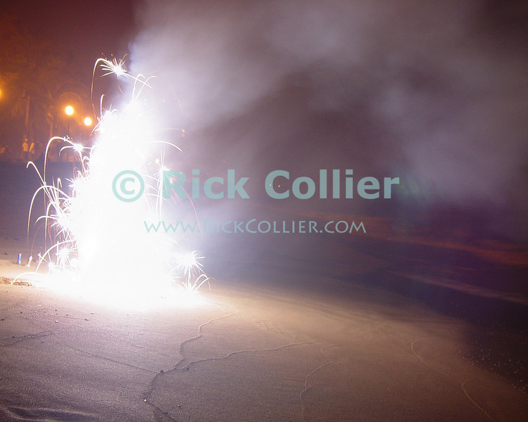 Local residents have set off a roman candle as they celebrate the New Year on the public beach near Kapiolani Park.  Waikiki, Honolulu, Oahu, Hawaii.<br /> <br /> <br /> <br /> <br /> <br /> <br /> Hawaii Hawai'i Honolulu Waikiki beach night lights reflection new year fireworks
