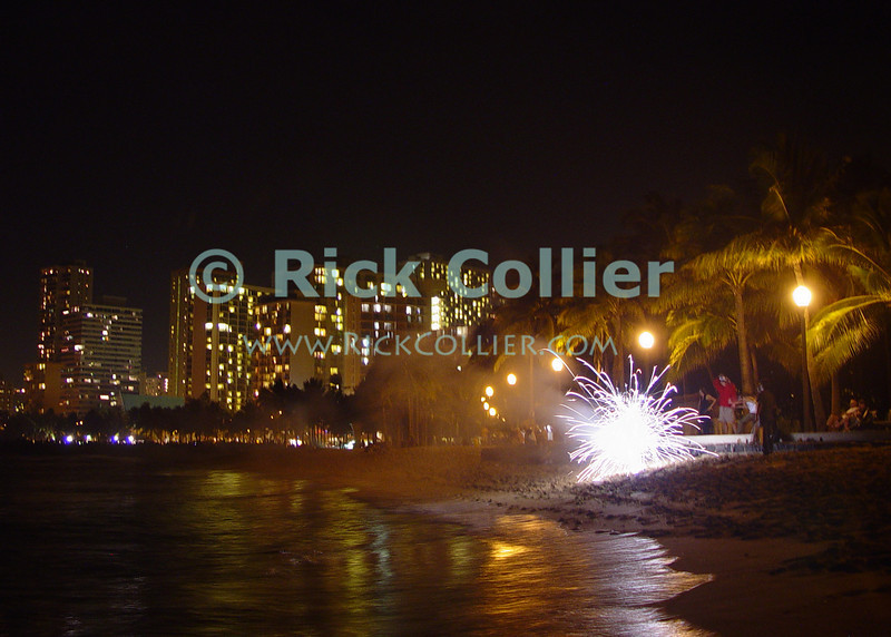 Honolulu is lit up in the background as local residents set off new year fireworks, at the public beach near Kapiolani Park in Waikiki.  Oahu, Hawaii.<br /> <br /> <br /> <br /> <br /> <br /> <br /> Hawaii Hawai'i Honolulu Waikiki beach night lights reflection new year fireworks
