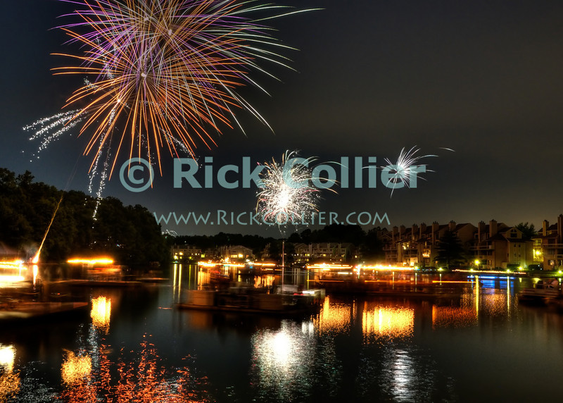 """US Independence Day Fireworks over Lake Thoreau, Reston, Virginia.  As dark falls, everyone who has a boat or floating dock embarks to enjoy the show as lakeside residents treat one another to a spectacular impromptu fireworks show over the lake.  © Rick Collier<br /> <br /> <br /> <br /> <br /> <br /> """"United States""""; US; USA; Virginia; VA; Reston; Thoreau; """"Lake Thoreau""""; """"Independence Day""""; Independence; """"Fourth of July""""; """"4th of July""""; """"July 4""""; """"July 4th""""; lake; celebration; party; reflection; fireworks; display; show; """"fireworks display""""; boat; boats; barge; dock; """"national day""""; patriotic; patriotism;"""
