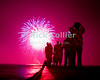 Tourists and locals gather on a jetty at Waikiki beach to watch the fireworks on New Year's eve.  Waikiki, Honolulu, Oahu, Hawaii.<br /> <br /> <br /> <br /> <br /> <br /> <br /> Hawaii Hawai'i Honolulu Waikiki beach night lights reflection new year fireworks jetty