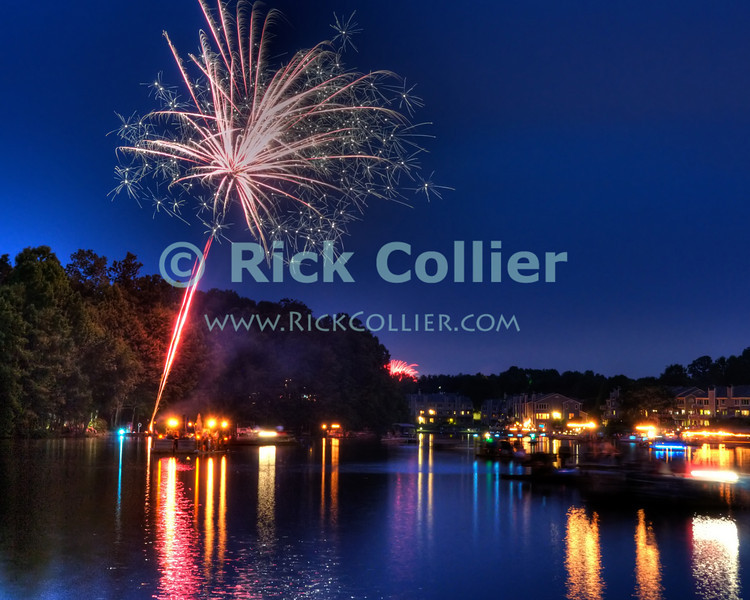 "US Independence Day Fireworks over Lake Thoreau, Reston, Virginia.  As dark falls, everyone who has a boat or floating dock embarks to enjoy the show as lakeside residents treat one another to a spectacular impromptu fireworks show over the lake.  © Rick Collier<br /> <br /> <br /> <br /> <br /> <br /> ""United States""; US; USA; Virginia; VA; Reston; Thoreau; ""Lake Thoreau""; ""Independence Day""; Independence; ""Fourth of July""; ""4th of July""; ""July 4""; ""July 4th""; lake; celebration; party; reflection; fireworks; display; show; ""fireworks display""; boat; boats; barge; dock; ""national day""; patriotic; patriotism;"