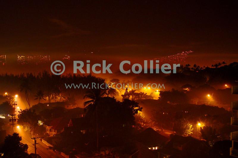 Smoke from New Year fireworks fills the streets around Kapiolani Park.  Waikiki, Honolulu, Oahu, Hawaii.  © Rick Collier<br /> <br /> <br /> <br /> <br /> <br /> <br /> <br /> Hawaii Hawai'i Oahu Honolulu Waikiki after dark night fireworks firework street lights streetlights smoke streets trees Kapiolani Park New Year celebration