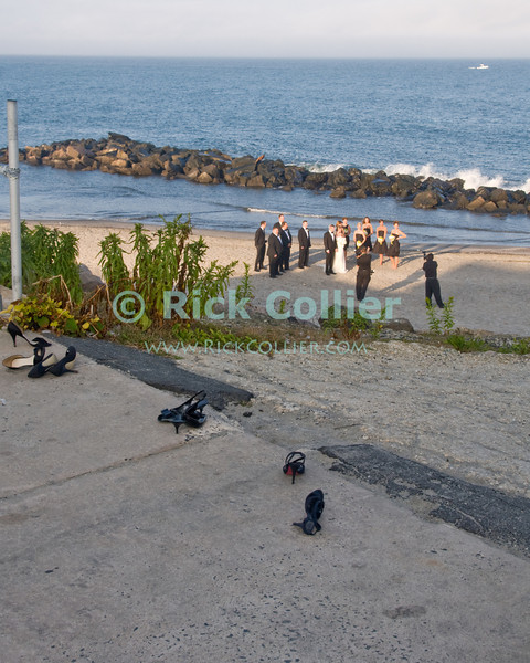 """Beach Wedding - As we were walking along the boardwalk, a young wedding party arrived for beach photos in the setting sun.  Allenhurst, New Jersey, USA.<br /> <br /> <br /> USA """"New Jersey"""" NJ Allenhurst beach breakwater jetty beach sand shoes romance wedding party marriage photography photo shoot Atlantic Ocean sunset"""