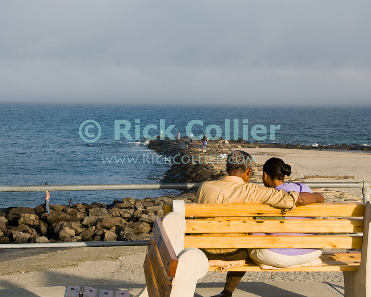 "A couple enjoys the sunset view of the Atlantic ocean.  Allenhurst, New Jersey, USA.<br /> <br /> <br /> USA ""New Jersey"" NJ Allenhurst beach Atlantic ocean view romance romantic couple bench"