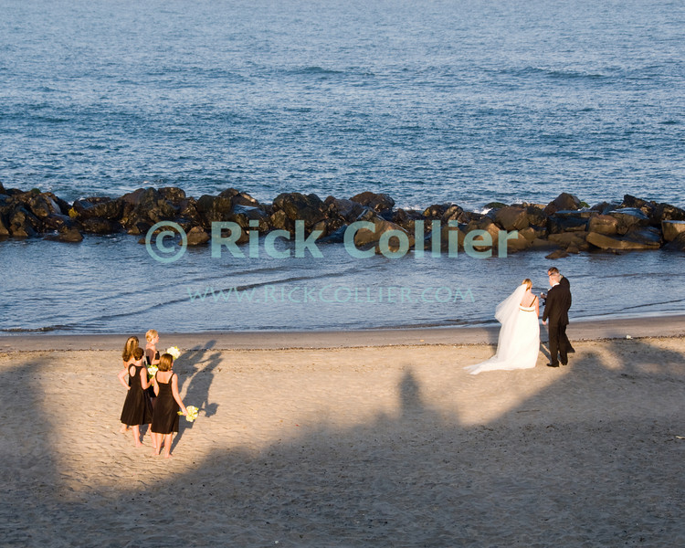 """Sunset Wedding"" - Bridesmaids watch the newlyweds in the last rays of sunlight.<br /> <br /> <br /> USA ""New Jersey"" NJ Allenhurst beach breakwater jetty beach sand shoes romance wedding party marriage photography photo shoot Atlantic Ocean sunset couples romantic bride groom bridesmaids"