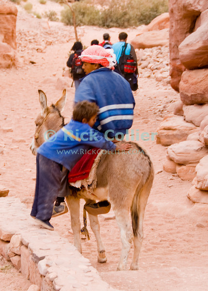 """""""He ain't heavy""""  -- A bedouin child waits for his brother to mount their mule, in the Wadi ad-Deir at the back of Petra, Jordan.  © Rick Collier<br /> <br /> <br /> <br /> Jordan Petra Nabatea Nabatean Rome Roman ruin archeology 'ancient world' antiquity cave 'cave dwelling' antiquities Bible Biblical civilization history historic desert stone cliff wall carve carved facade tourist tourism archeology valley path road hike trail desert necropolis arab bedouin child children donkey brother brothers"""
