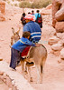 """He ain't heavy""  -- A bedouin child waits for his brother to mount their mule, in the Wadi ad-Deir at the back of Petra, Jordan.  © Rick Collier<br /> <br /> <br /> <br /> Jordan Petra Nabatea Nabatean Rome Roman ruin archeology 'ancient world' antiquity cave 'cave dwelling' antiquities Bible Biblical civilization history historic desert stone cliff wall carve carved facade tourist tourism archeology valley path road hike trail desert necropolis arab bedouin child children donkey brother brothers"