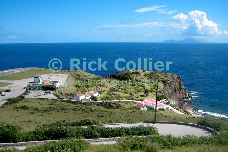 Saba - The airport's short runway was leveled by hand at the only flat spot on the island.  St. Eustatius is visible in the distance.  © Rick Collier
