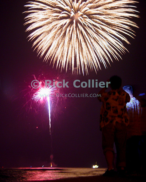 Tourists and locals gather on a jetty at Waikiki beach to watch the fireworks on New Year's eve.  Waikiki, Honolulu, Oahu, Hawaii.