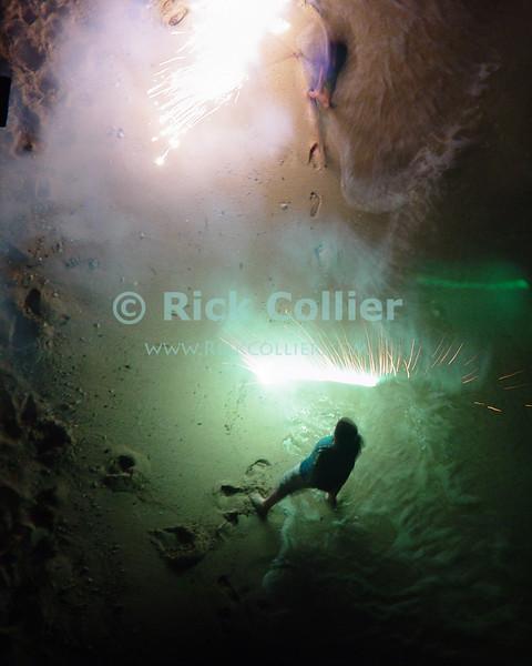 Kids play with sparklers on the beach.  Waikiki, Honolulu, Oahu, Hawaii.  © Rick Collier<br /> <br /> <br /> <br /> <br /> <br /> <br /> <br /> Hawaii Hawai'i Oahu Honolulu Waikiki after dark night fireworks sparklers play beach