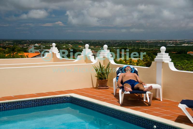 "Bonaire, Netherland Antilles -- A diver naps during the surface interval by the pool at the <a href=""http://www.villasafir.com/"">Villa Safir B&B</a>, with a spectacular view of Bonaire.  © Rick Collier     Bonaire; ""Netherlands Antilles""; Caribbean; tropic; tropical; vacation; destination; scuba; diving; dive; ""scuba diving""; ""Villa Safir""; B&B; view;"