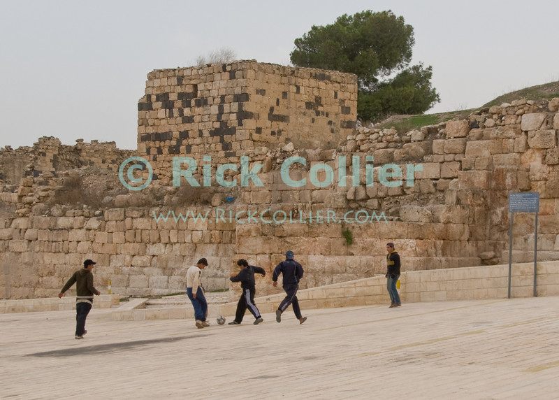 Umm Qais, northwestern Jordan:  Local kids play soccer (football) on the sloping parking area below the walls and ruins at the biblical town of Gadara.  © Rick Collier<br /> <br /> <br /> <br /> Jordan 'Umm Qais' Ottoman Roman Gadara Gadarenes Bible Biblical ruin ruins 'ancient world' archeology 'archeological site' antique kids children child soccer game football antiquity