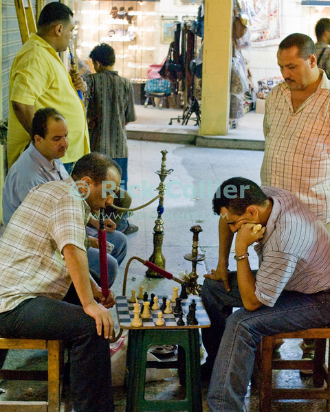Chess players, smoking.  Two popular pastimes are frequently seen on the streets of Cairo, as men meet after work to smoke the water pipe and play chess or backgammon.  The Khan el-Khalili in central Cairo was once the market terminus for caravans crossing the Sahara.  Today, it is a warren of narrow streets and alleys, crowded with restaurants, tea rooms, stalls, and shops selling everything from jewelry to clothing to souvenirs and home decorations.  © Rick Collier<br /> <br /> <br /> <br /> <br /> <br /> <br /> Egypt Cairo Khan 'Khan el-Khalili' 'Khan al-Khalili' shop store Islamic Cairo stalls stands shopping tourism tourist historic history chess tobacco smoke smoking playing play game games gamers relaxation street group friends friendship pipe water pipe 'water pipe'