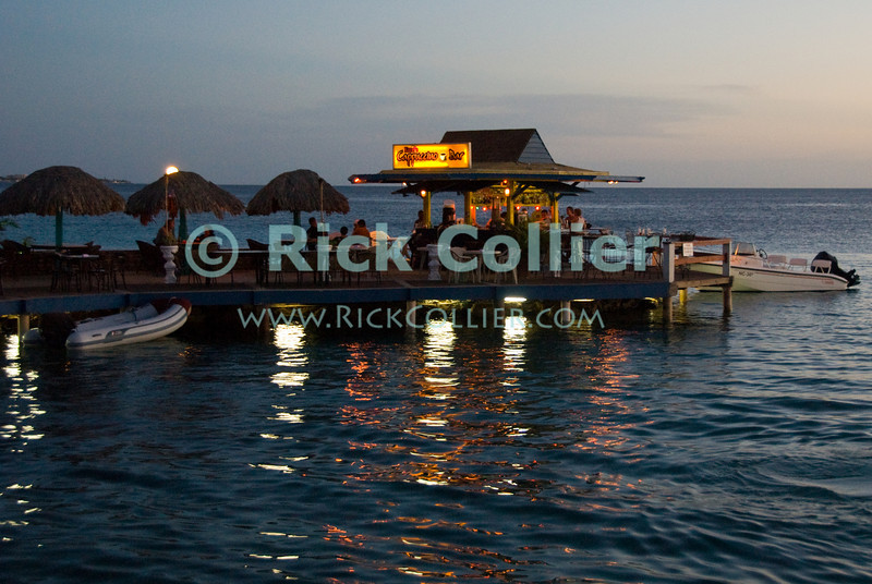 """Kralenkijk, Bonaire, Netherland Antilles -- The over-water cappuccino bar is a popular place to rest, right at the center of the waterfront in Kralendijk.  © Rick Collier<br /> <br /> <br /> <br /> Bonaire; """"Netherlands Antilles""""; Caribbean; tropic; tropical; vacation; destination; Kralendijk; coffee; capuccino; pier; dock; water; waterfront; sunset; evening; lights;"""