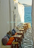 Mikonos, Greece.  Cushioned benches and small table await customers at a Mikonos alleyway cafe overlooking the ocean.  © Rick Collier<br /> <br /> <br /> <br /> <br /> <br /> <br /> Greece Mikonos Mykonos Greek cafe restaurant ocean view Aegean sea tables cushions chairs stools