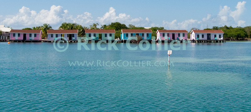 Cabanas at Hugh Parkey's Dive Connection, Belize.  Small guest cottages are perched on stilts overlooking the beautiful blue and green waters of Spanish Lookout Caye, near Belize City and Turneffe Atoll, Belize.  © Rick Collier