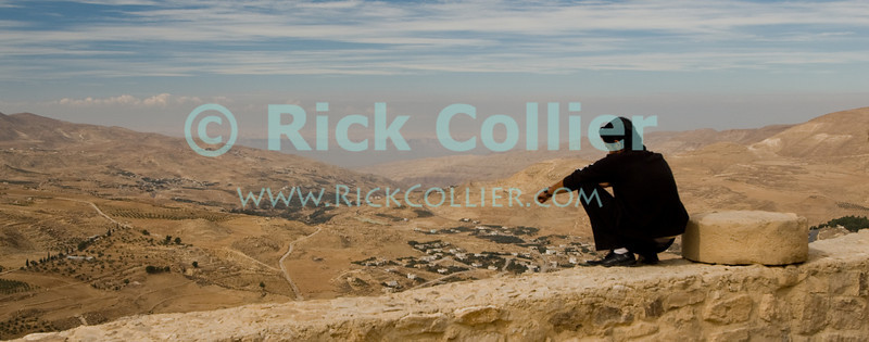 High Perch.  A young man perches right on the edge of Karak Castle's battlements, atop a sheer face several hundred feet above the Wadi al-Karak, below.  The bluffs on the Israeli side of the Dead Sea are clearly visible in the distance.  According to legend, the ancient Biblical condemned cities of Sodom and Gomorrah were between Karak and the Dead Sea, in this view.  The Crusader castle at Karak guarded the eastern border of the Kingdom of Jerusalem after the first Crusade. © Rick Collier<br /> <br /> <br /> <br /> <br /> Jordan Karak al-Karak castle crusader crusades knights fort fortress history historic tourist tourism antiquities 'Kingdom of Jerusalem' battlement battlements walls keep chapel ruin ruins view panorama cross-country