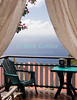 Saba - The elevated deck view from our room at Scout's Place, Windwardside, allows us to look out to the Caribbean, across the roofs of houses below.  Our deck is framed by curtains and bougainvillea .  © Rick Collier