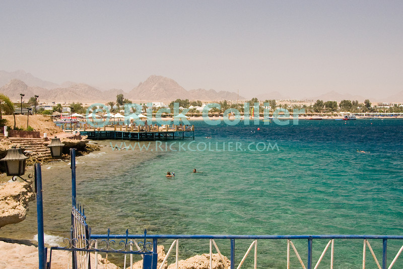 Sharm el-Sheikh, the Sinai, Egypt.  Tourists enjoy the views and the water.  Hotels line the shores of the Red Sea at Sharm el-Sheikh, with the barren mountains of the Sinai beyond.  © Rick Collier<br /> <br /> <br /> <br /> <br /> <br /> Egypt 'Red Sea' 'Ras Mohammed' Sharm 'Sharm el-Sheikh' 'Sharm al-Shaykh' seashore Sinai arab sea view hotel tourist tourism swim swimming beach