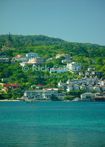 Amanoka Villa, Discovery Bay, Saint Ann Parish, Jamaica.  A lone fisherman rows across the harbor below the local town.  The town of Discovery Bay (also known as Dry Harbor Bay), which spreads across the sides of the Dry Harbour Mountains, overlooking the blue-green waters of the harbor in Discovery Bay, Jamaica.  © Rick Collier<br /> <br /> <br /> <br /> <br /> <br /> Jamaica Discovery Bay Dry Harbor Bay Amanoka Villa tropical paradise swimming pool beach relaxation ocean water reflection town buildings shops harbor hills trees mountain gazebo dock docks calm blue green water
