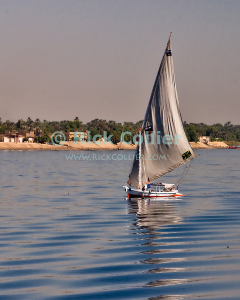 """Nile River, Egypt -- A felucca first thing in the morning. © Rick Collier / RickCollier.com.<br /> <br /> <br /> <br /> travel; vacation; tour; tourism; tourist; destination; Egypt; boat; boats; sailboat; shore; river; Nile; """"Nile River""""; sail; sailing; felucca;"""