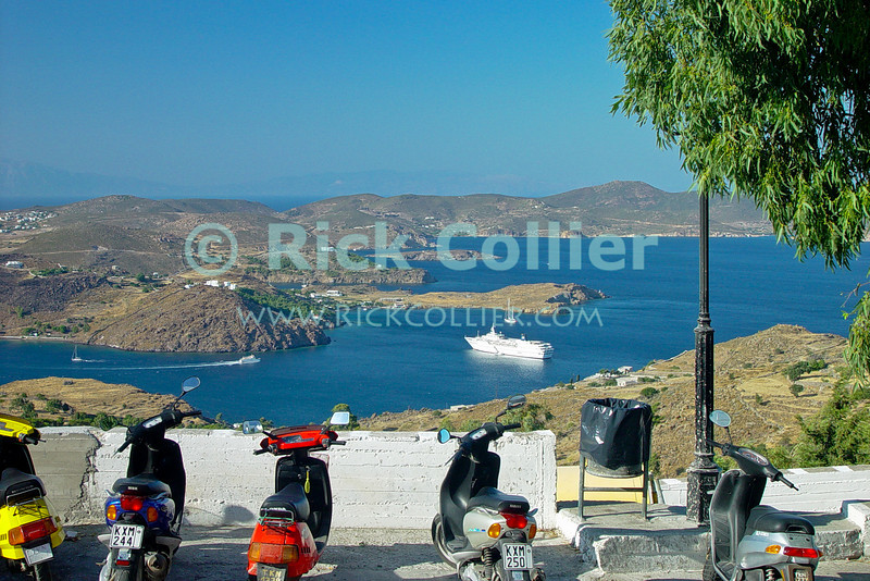 Patmos, Greece.  The harbor opens out in a spectacular view from a roadside overlook near the monestary on Patmos.  © Rick Collier<br /> <br /> <br /> <br /> <br /> <br /> Greece Patmos cross religion Christian John Saint John the Theologian 'St John' revelation Bible Biblical Book of Revelations cave holy site shrine olive tree window windows monestary courtyard window windows door doors narrow alley alleyway cruise ship motorcycle motorbike view views harbor inlet ocean Aegean Sea