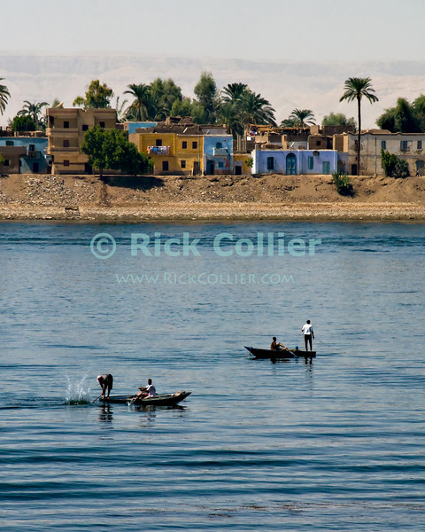 """Nile River, Egypt -- Fishermen at work in the Nile River.  Each boat will string a net, then the boatmen will beat the water with planks or oars to drive fish into the nets (near Luxor, Egypt). © Rick Collier / RickCollier.com.<br /> <br /> <br /> <br /> <br /> <br /> <br /> travel; vacation; tour; tourism; tourist; destination; Egypt; Nile; """"Nile River""""; boat; town; village; fishing; fisherman;"""