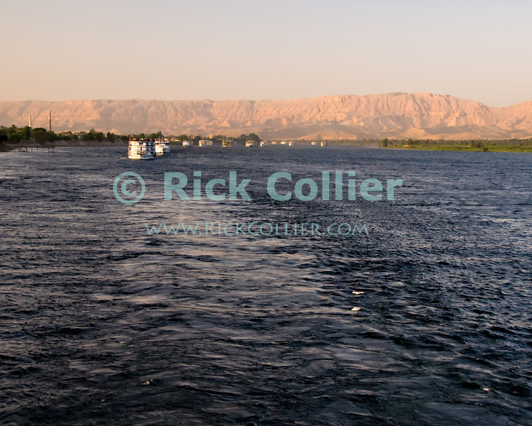 """Nile River, Egypt -- Nile River cruise boats in line cruising in line South on Nile River excursion cruises (near Luxor, Egypt). © Rick Collier / RickCollier.com.<br /> <br /> <br /> <br /> travel; vacation; tour; tourism; tourist; destination; Egypt; Nile; """"Nile River""""; boat; ships; ship; boat;"""