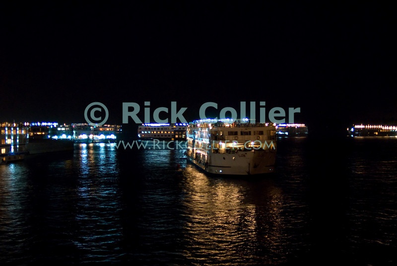 """Nile River, Esna, Egypt -- Cruise ships maneuver for position to pass through the locks at the Esna dam after dark.    © Rick Collier / RickCollier.com.<br /> <br /> <br /> <br /> travel; vacation; tour; tourism; tourist; destination; Egypt; Nile; """"Nile River""""; boat; boats; Esna; lock; """"Esna dam""""; ship; ships; cruise; """"cruise ship"""""""