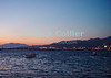 Mikonos, Greece.  Mikonos harbor catches the last rays of the setting sun.  © Rick Collier<br /> <br /> <br /> <br /> <br /> <br /> <br /> Greece Mikonos Mykonos tour tourist tourism small Greek harbor ships ship boat boats light lights evening night sunset reflections