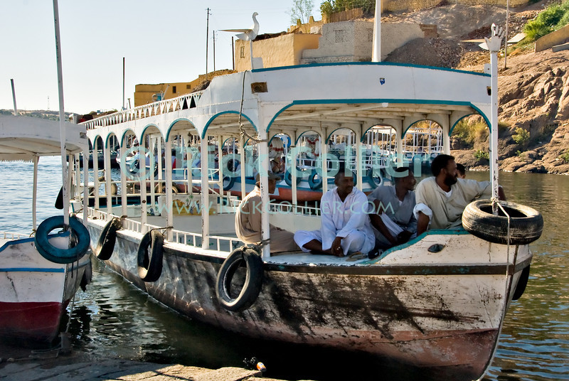 """Aswan, Egypt -- Philae Temple -- Boatmen await tourist """"fares"""" for the trip across the lake to Agilika Island, site today of the Philae Temple (""""Temple of Philae"""").  The original island location of Philae was submerged by the building of the Aswan High Dam, so the temple was relocated and is now visited on the island Agilika.  The island temple can only be reached by hiring these """"water taxis."""" © Rick Collier / RickCollier.com.<br /> <br /> <br /> travel; vacation; tour; tourism; tourist; destination; Aswan; dam; """"Aswan dam""""; """"High Dam""""; Nile; river; """"Nile River""""; Philae; """"Philae Temple""""; Hathor; Ptolemy; Ptolemaic; Agilika; temple; hieroglyphic; hieroglyph; """"ancient Egypt""""; boat; boatmen; boats; ferry; taxi;"""